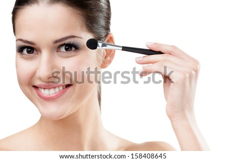 Woman applying make-up with cosmetic brush, isolated on white. Beauty procedures - stock photo