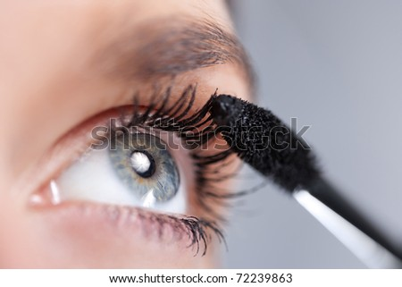 Woman applying mascara on her eyelashes. Short depth of field
