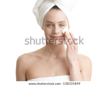 Woman applying moisturizer cream on face against white background. Close-up fresh woman face. - stock photo