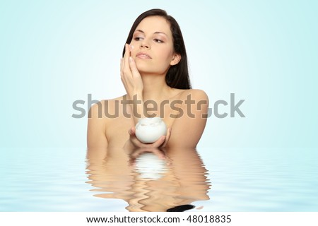 Woman applying moisturizer cream on face. Close-up fresh woman face. - stock photo