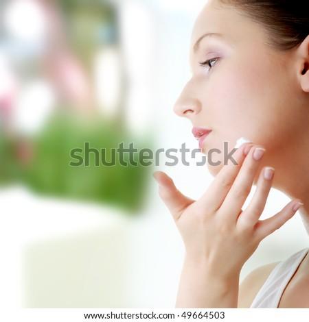 Woman applying moisturizer cream on face. Close-up fresh woman face. - stock photo