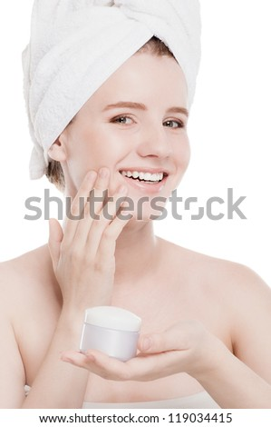 Woman applying moisturizer cream on face. Close-up fresh woman face isolated on white