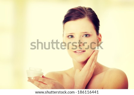 Woman applying moisturizer cream on face. Close-up on woman face.  - stock photo