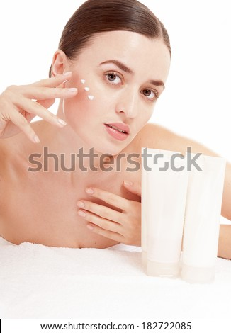 Woman applying moisturizer cream on face. Skin care concept. - stock photo