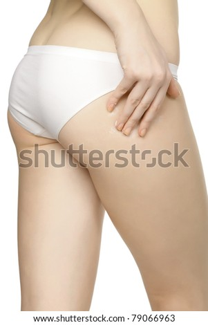 Woman applying moisturizer cream on legs, isolated on white background - stock photo