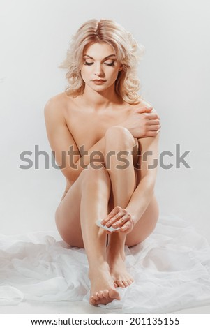 Woman applying moisturizer cream on the legs over white background - stock photo