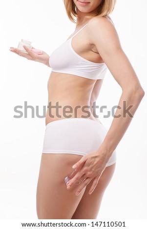 Woman applying moisturizer cream on thigh - stock photo