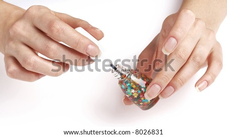 woman applying nailpolish with small colorful stars, party manicure