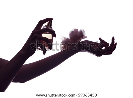 woman applying perfume on her wrist, holding gold perfume bottle - stock photo