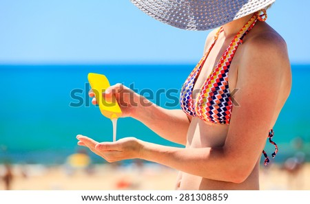 woman applying protective lotion before sunbathing at beach - stock photo