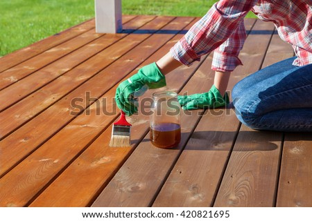 Woman applying protective varnish or wood oil on a patio wooden floor, house maintenance concept. Before and after effect - stock photo