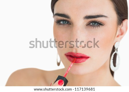 Woman applying red lip gloss while having a porcelain face - stock photo