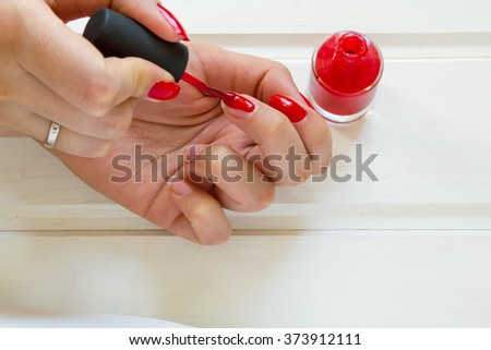 Woman applying red nail polish.  manicure on white background. Female hand. - stock photo