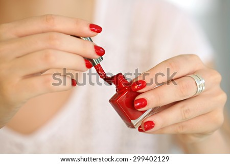 Woman applying red nail polish on her fingers - focus on the brush. - stock photo