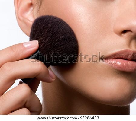 woman applying rough on cheek - macro shot - stock photo
