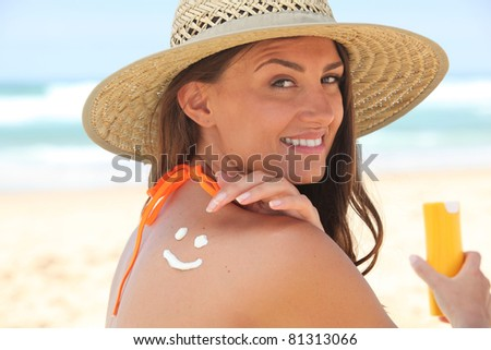 Woman applying suncream at the beach - stock photo