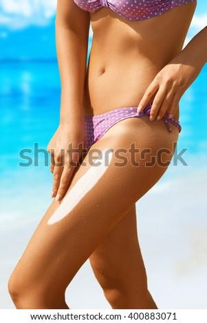 Woman applying sunscreen on her legs. Solar cream sun protection concept. - stock photo