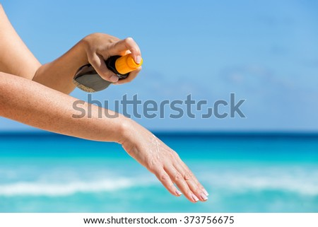 Woman applying sunscreen protection cream against turquoise caribbean sea water and blue sky. Tropical summer vacation concept - stock photo