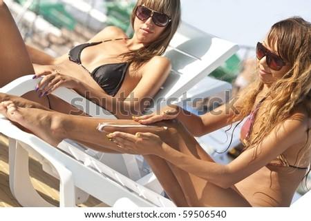 Woman applying suntan lotion at aquapark - stock photo