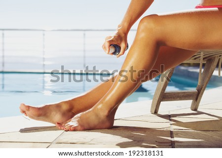 Woman applying suntan spray onto her legs. Female sitting on recliner chair by the swimming pool sunbathing. - stock photo