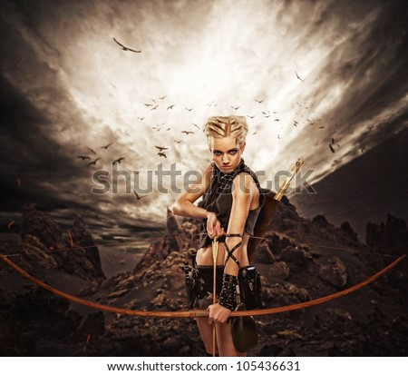 Woman archer against storm over rocks - stock photo