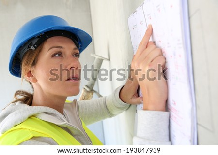 Woman architect reading construction plan