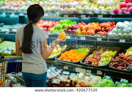 Woman are choosing fruit in supermarkets - stock photo