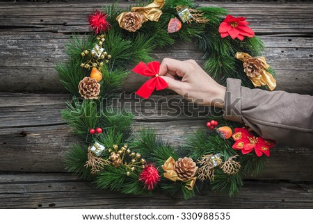 Woman arm is hanging red bow on wooden log cabin wall with green holiday wreath - stock photo