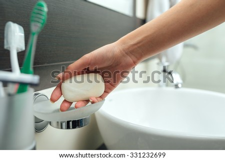 woman arm takes a soap to wash