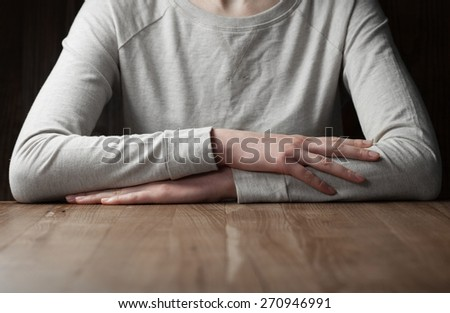 woman arms folded over wooden table