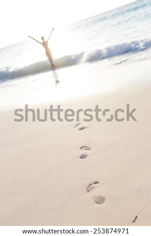 Woman, arms raised, enjoying summer on tropical beach in in sunset. Beautiful caucasian model wearing bikini on vacations on sandy beach. Footprints in sand.  - stock photo