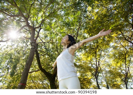 woman arms raised enjoying the fresh air in green forest. - stock photo