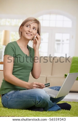 Woman arranging hotel reservation from home, using laptop, mobilephone and credit card.