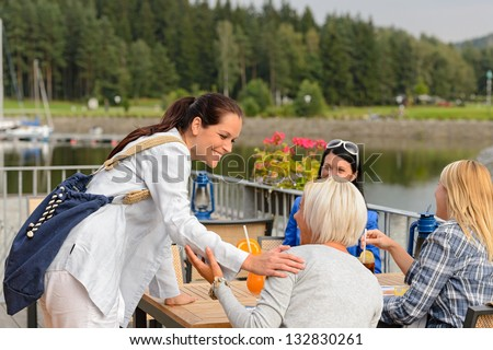 Woman arriving at outdoor restaurant terrace to her girl friends - stock photo