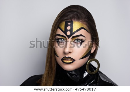woman art make up. Creative dark black and gold golden make-up, conceptual idea for Halloween. body art painting. Professional photo, gray background horizontal banner. Big round earring leather scarf