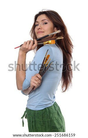 Woman artist holding her brushes in each hand and looking over her shoulder proudly against an isolated background