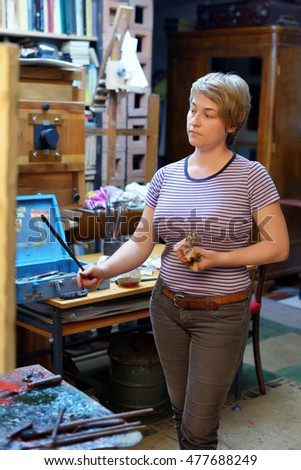 Woman artist paints in her workshop.