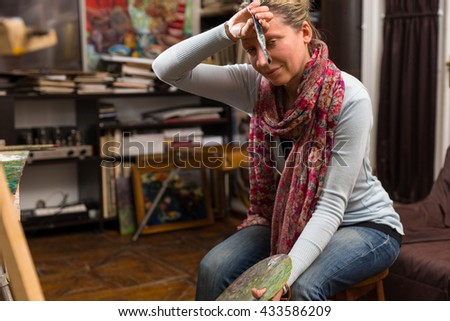 Woman artist pausing to wipe her forehead with a paintbrush in her hand as she sits back to analyse a canvas she is working on on an easel in an art studio or gallery - stock photo