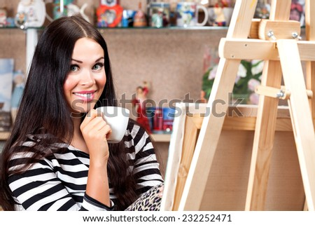 Woman artist with a cup of coffee or tea - stock photo