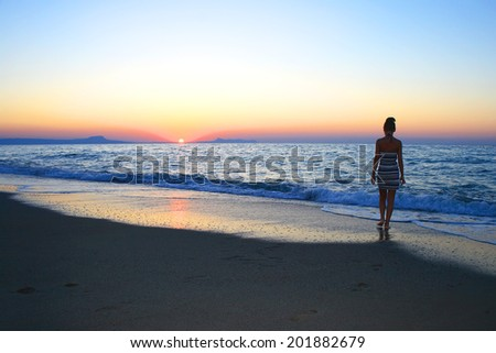 Woman as silhouette on the beach at sunset - stock photo