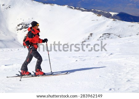 Woman ascending on touring skis in sunny winter day - stock photo