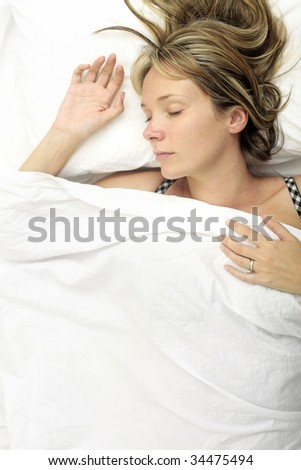 Woman asleep in a bed with white sheets