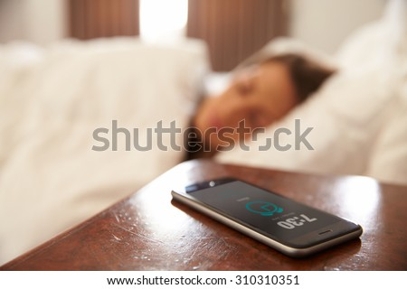 Woman Asleep In Bed Woken By Alarm On Mobile Phone - stock photo