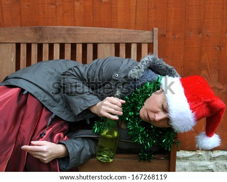woman asleep on bench outside, after Christmas party, wearing santa hat and tinsel, holding wine bottle. - stock photo