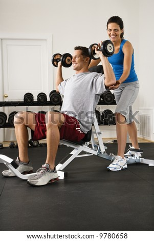 Woman assisting man lifting weights at gym. - stock photo