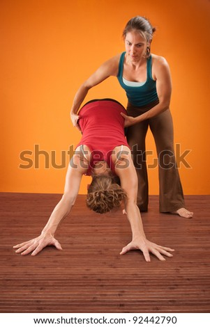 Woman assists her partner in a yogasana workout - stock photo