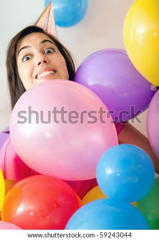 Woman at a birthday party surrounded by colorful balloons - stock photo