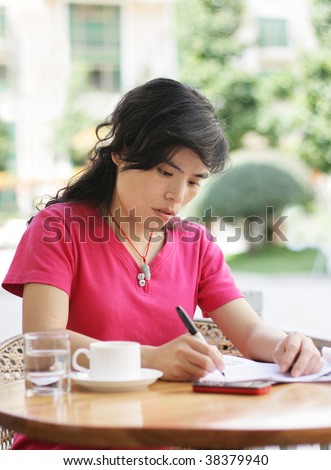 woman at a cafe writing on a sheet of paper