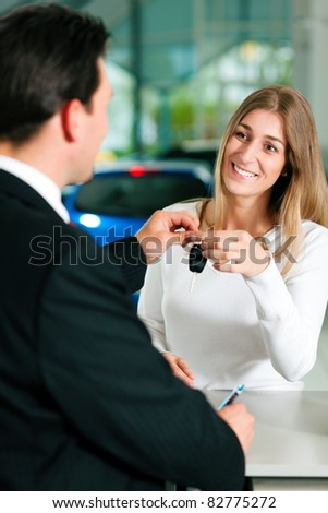 Woman at a car dealership buying an auto, the sales rep giving her the key - stock photo