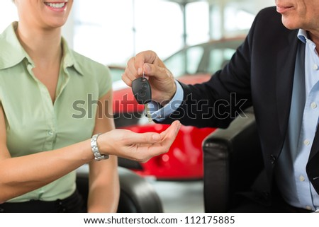 Woman at a car dealership buying an auto, the sales rep giving her the key, macro shot with focus on hands and key - stock photo